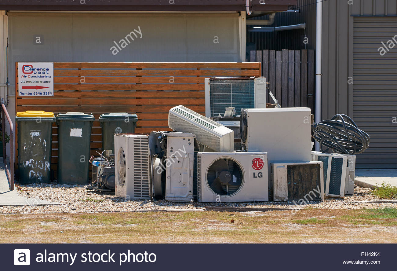 A pile of air-conditioners / a/c units, placed next to several garbage bins, on the footpath, in the summer sun; in Yamba, NSW, Australia. - Stock Image