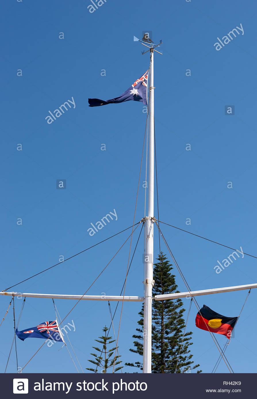 An Australian flag flies high above an Aboriginal and a NZ flag, on a large white flagpole; on Australia Day / Invasion Day in Yamba, NSW, Australia. - Stock Image