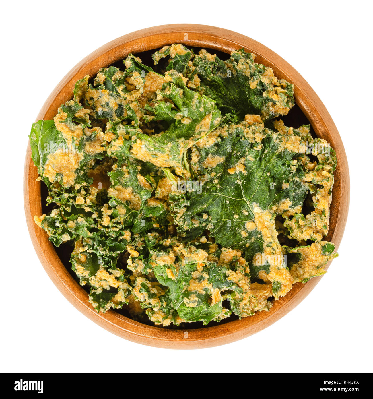 Homemade kale chips in wooden bowl. Dehydrated green leaf cabbage, coated with blended spices, nuts and vegetables. Snack and potato chip substitute. - Stock Image