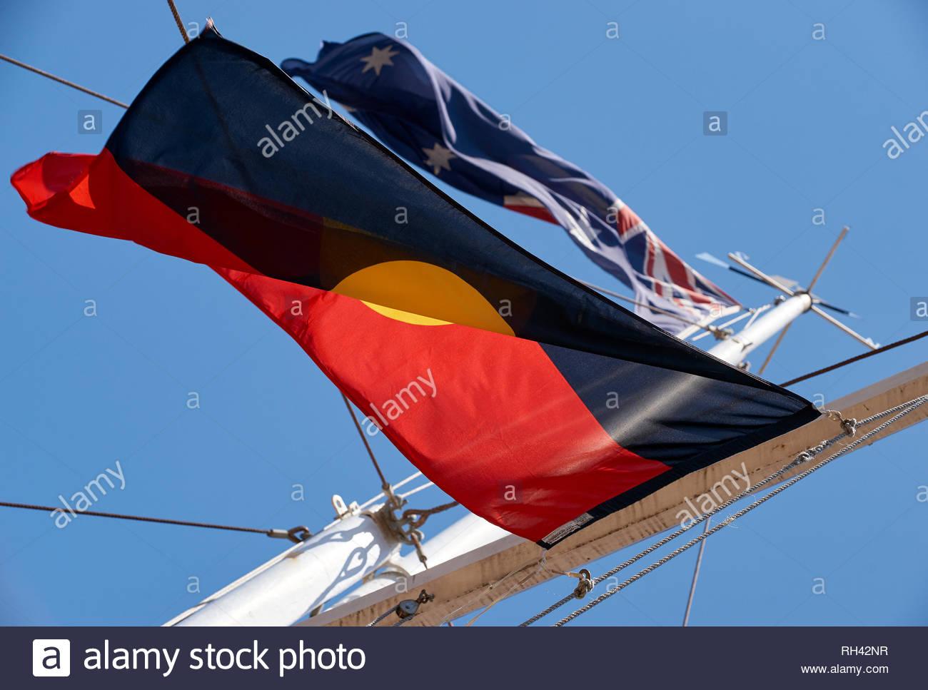 An Australian flag flies symbolically, high above an Aboriginal flag, on a white flagpole; on Australia Day / Invasion Day in Yamba, NSW, Australia. - Stock Image