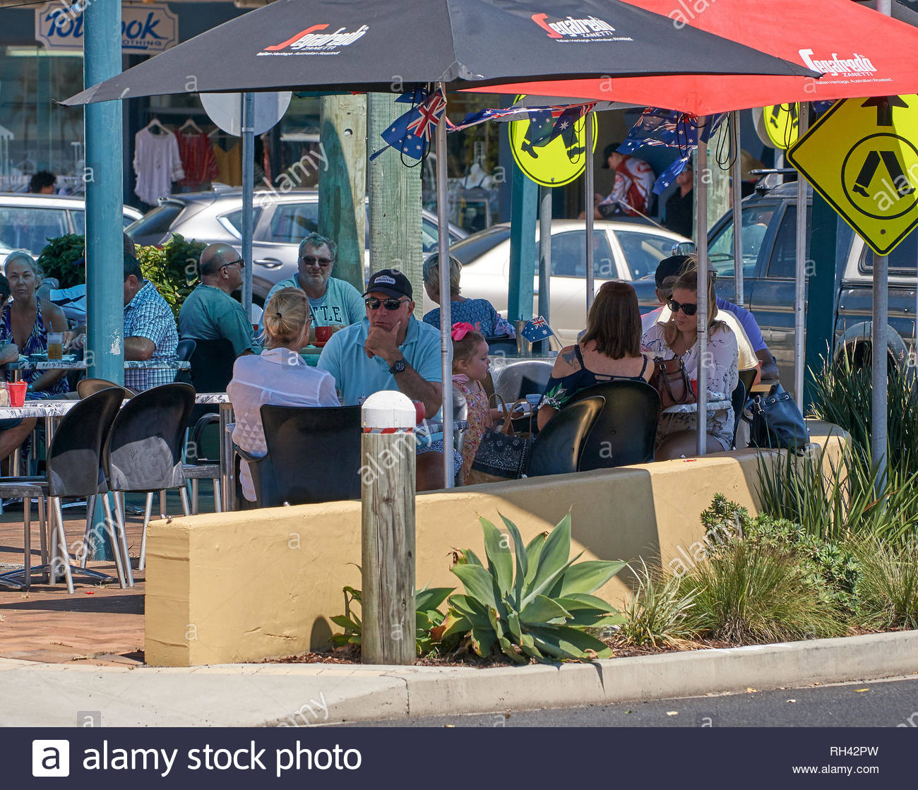 White Australians sitting at tables under umbrellas, at a popular coffee shop - cafe - on Australia Day / Invasion Day in Yamba, NSW, Australia. - Stock Image