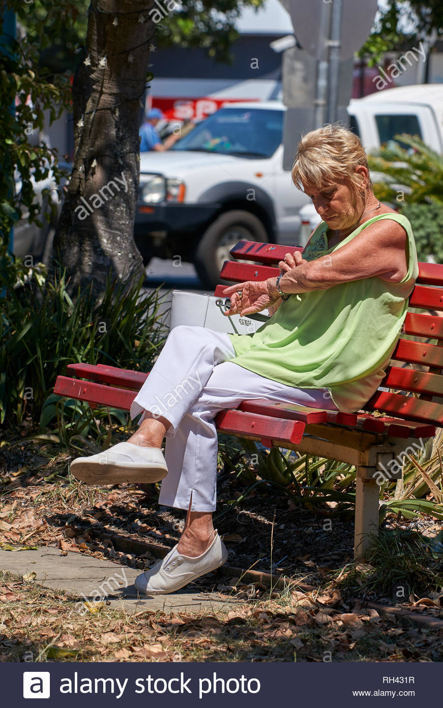 An older woman sitting on a red bench-seat, picking at her forearm in the sun and wearing pale green and white clothes and shoes; in Yamba, Australia. Stock Photo