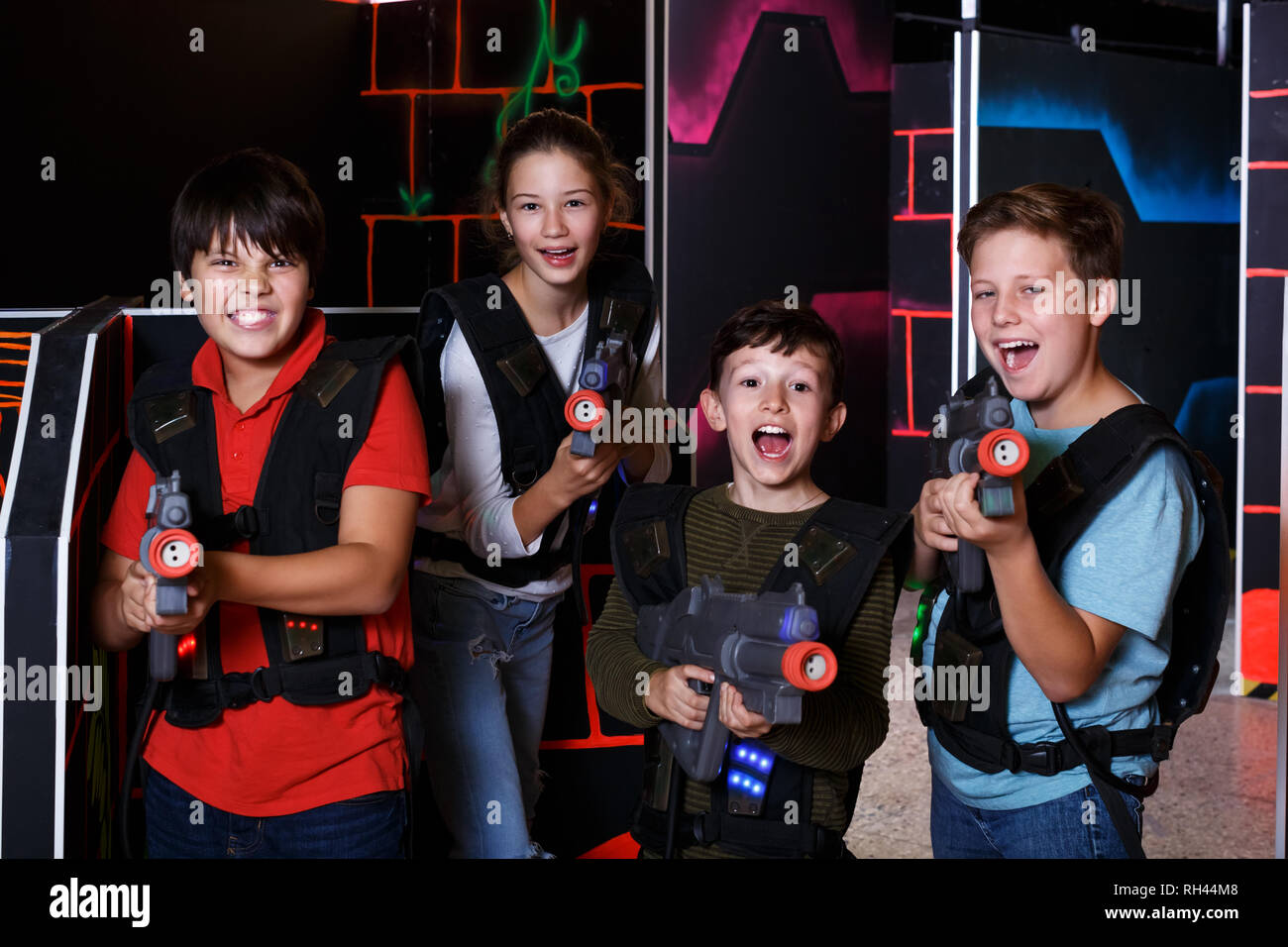 Smiling kids with laser pistols posing together in dark