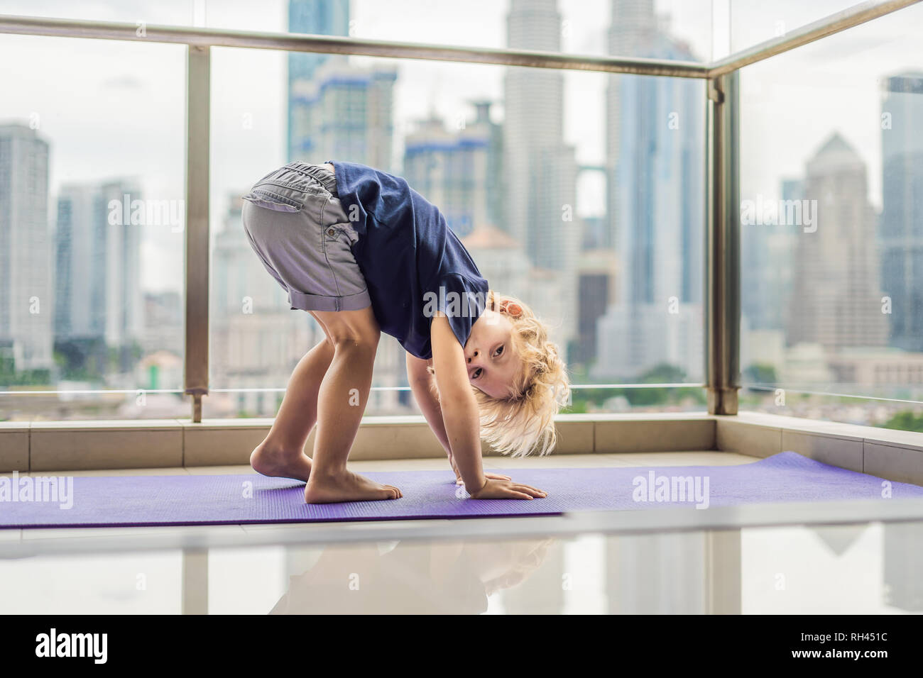 Happy little boy is practicing yoga on his balcony with a panoramic view of the big city - Stock Image
