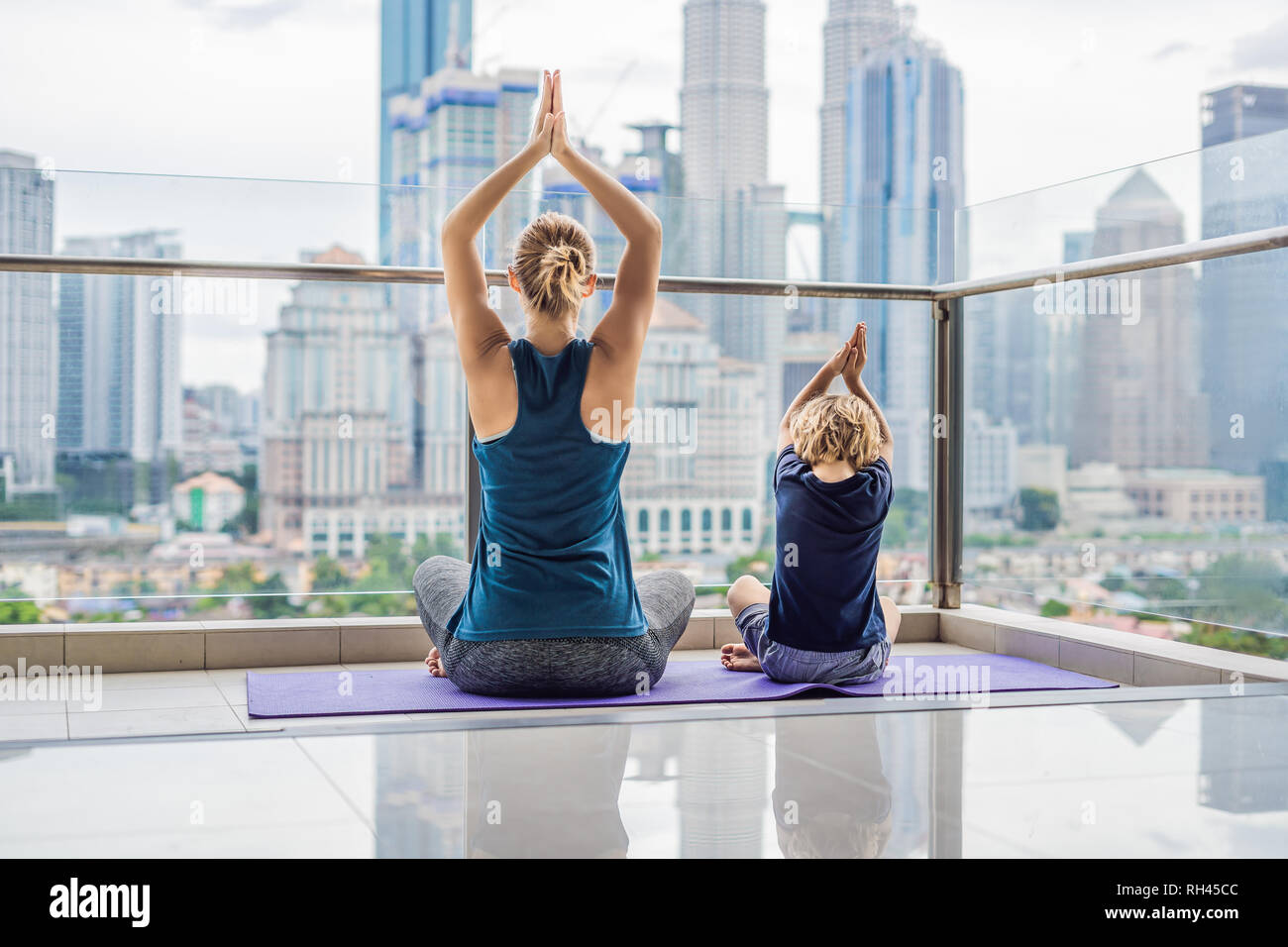 Mom and son are practicing yoga on the balcony in the background of a big city. Sports mom with kid doing morning work-out at home. Mum and child do Stock Photo