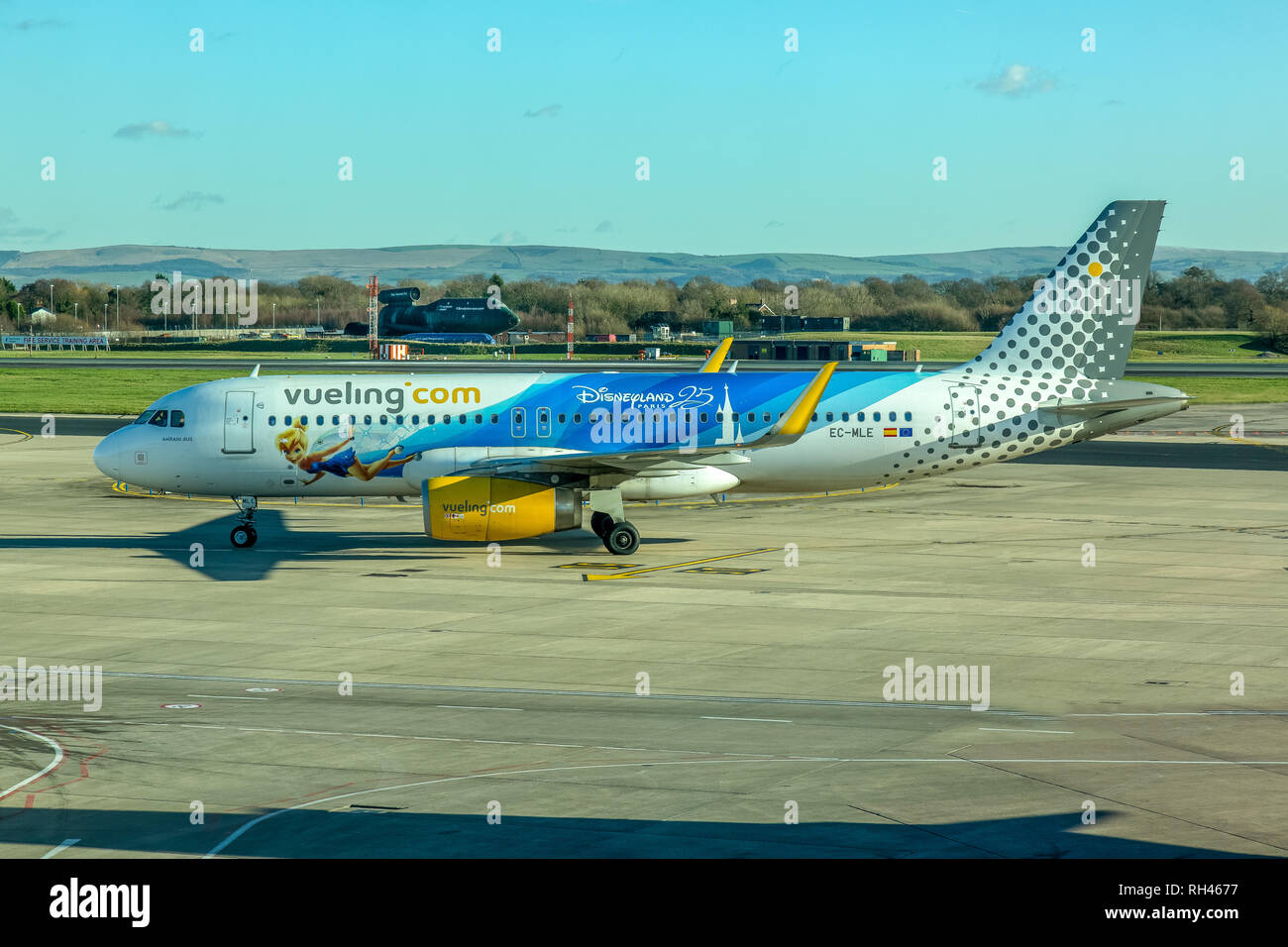 A Vueling Airlines Airbus A320 aircraft, registered EC-MLE, and showing a livery advertising 25 years of Disneyland Paris, at Manchester Airport. - Stock Image