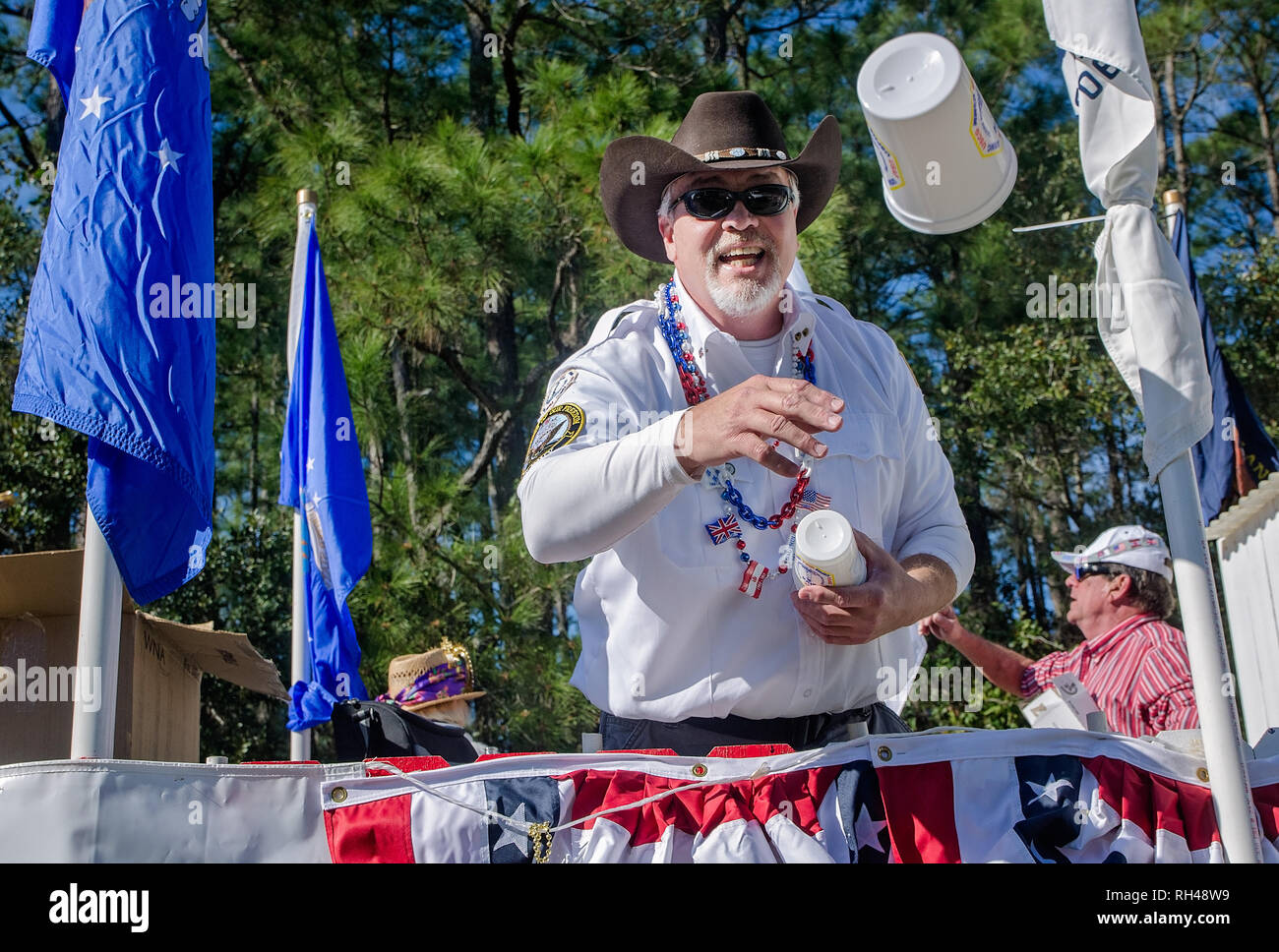 895689945c4 A member of the Dauphin Island Veterans Association throws a Mardi Gras cup  during the People s