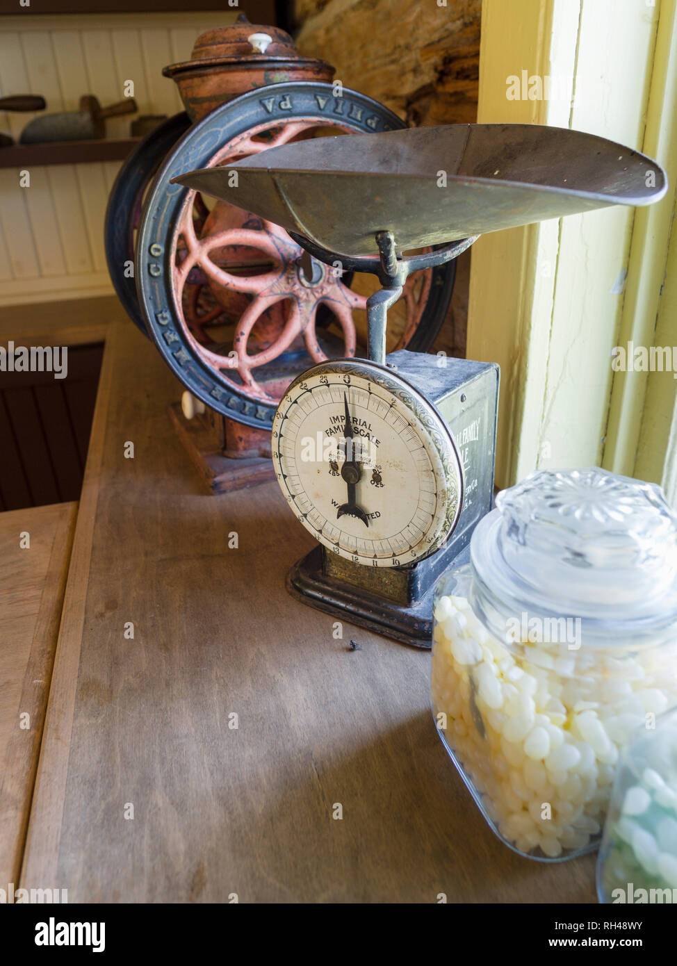 General Store: scale, grinder, jelly beans: The window of an old General Store in Cumberland village featuring jars of jelly beans, an old imperial scale and a hand cranked coffee grinder. - Stock Image