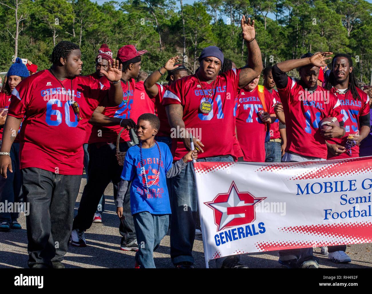 Football players march in the Krewe de la Dauphine parade in Dauphin Island, Alabama, Jan. 17, 2015, kicking off Mobile's Mardi Gras season. - Stock Image