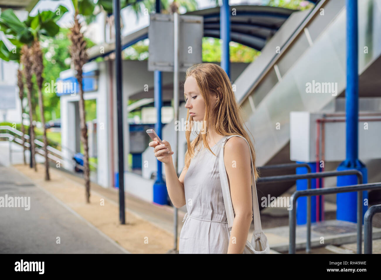 Woman using phone app for taxi ride hailing service or using phone app to find directions and guide during travel. Girl tourist on street - Stock Image