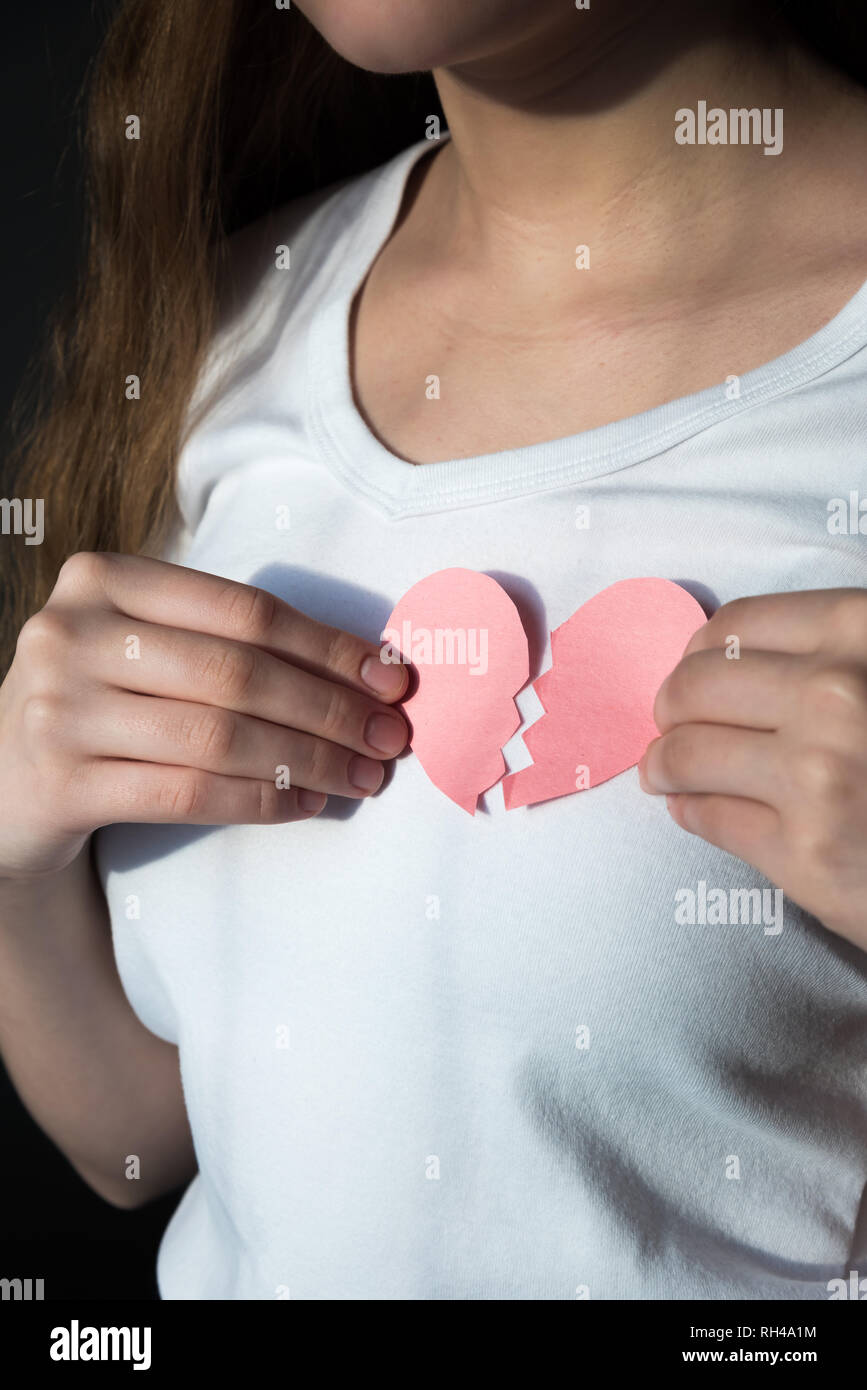 Close-up of broken heart held against woman's chest - Stock Image
