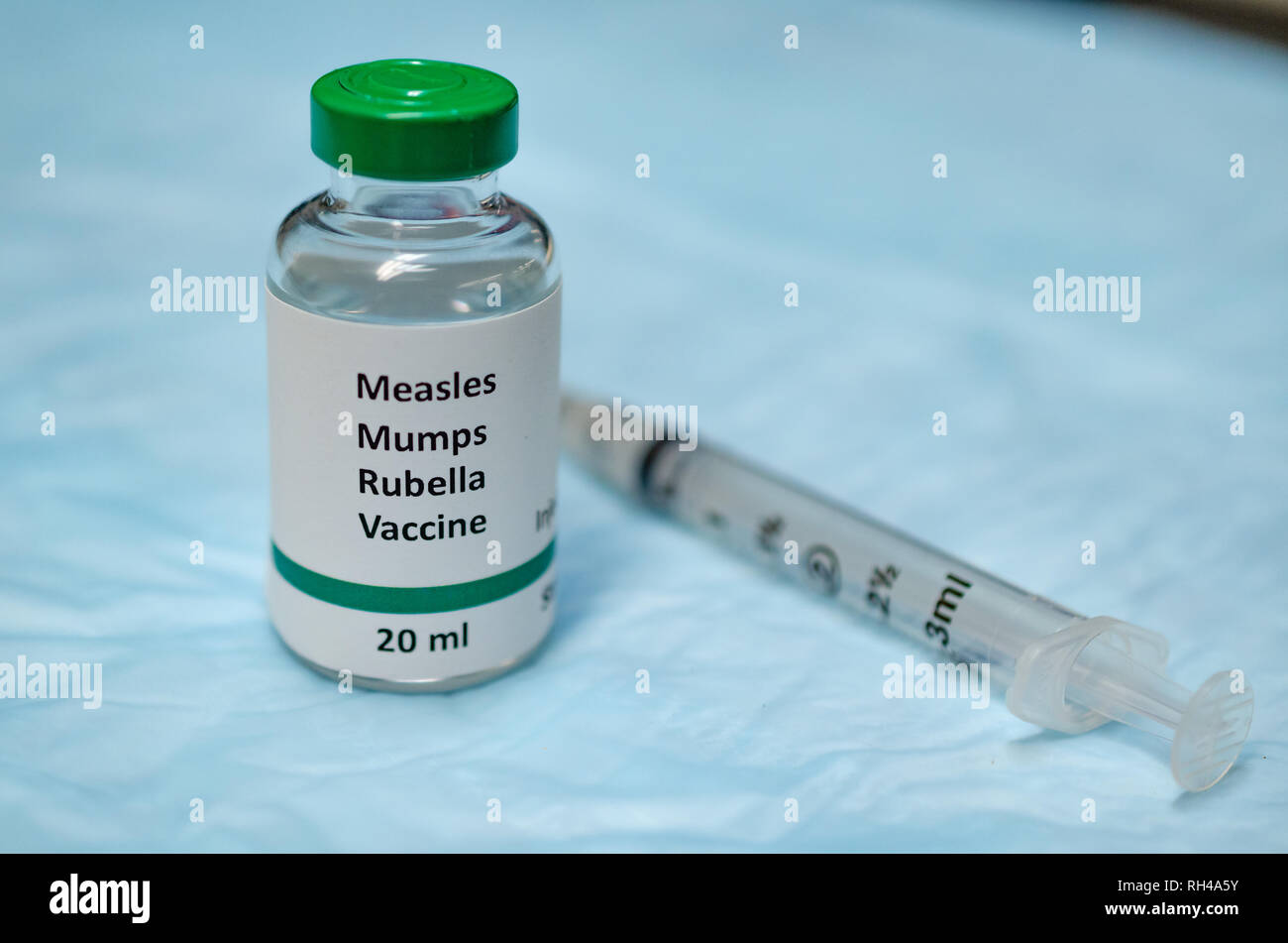 Measles, mumps and rubella combined vaccine vial with injection syringe - Stock Image