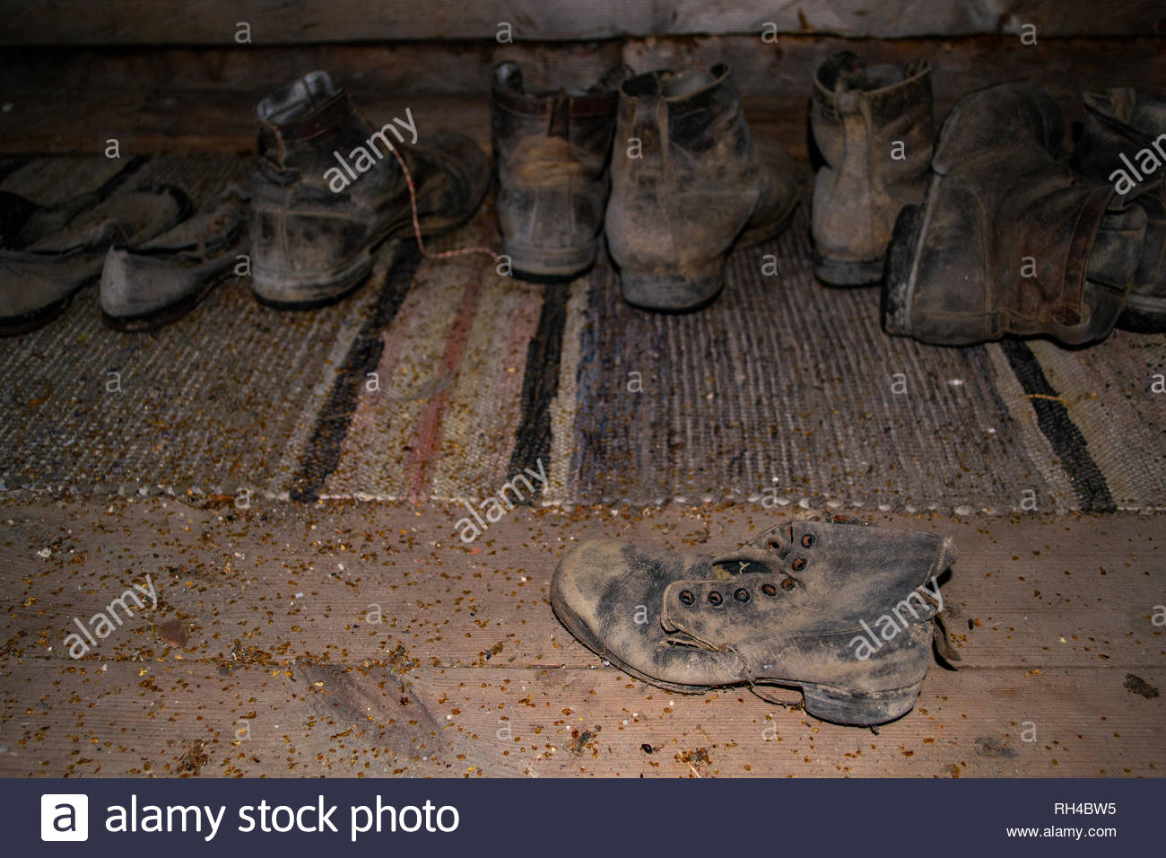 Closeup of old vintage shoes and leather boots in a wooden farm house attic. Selective focus on one leather boot in the front, blurred background. - Stock Image