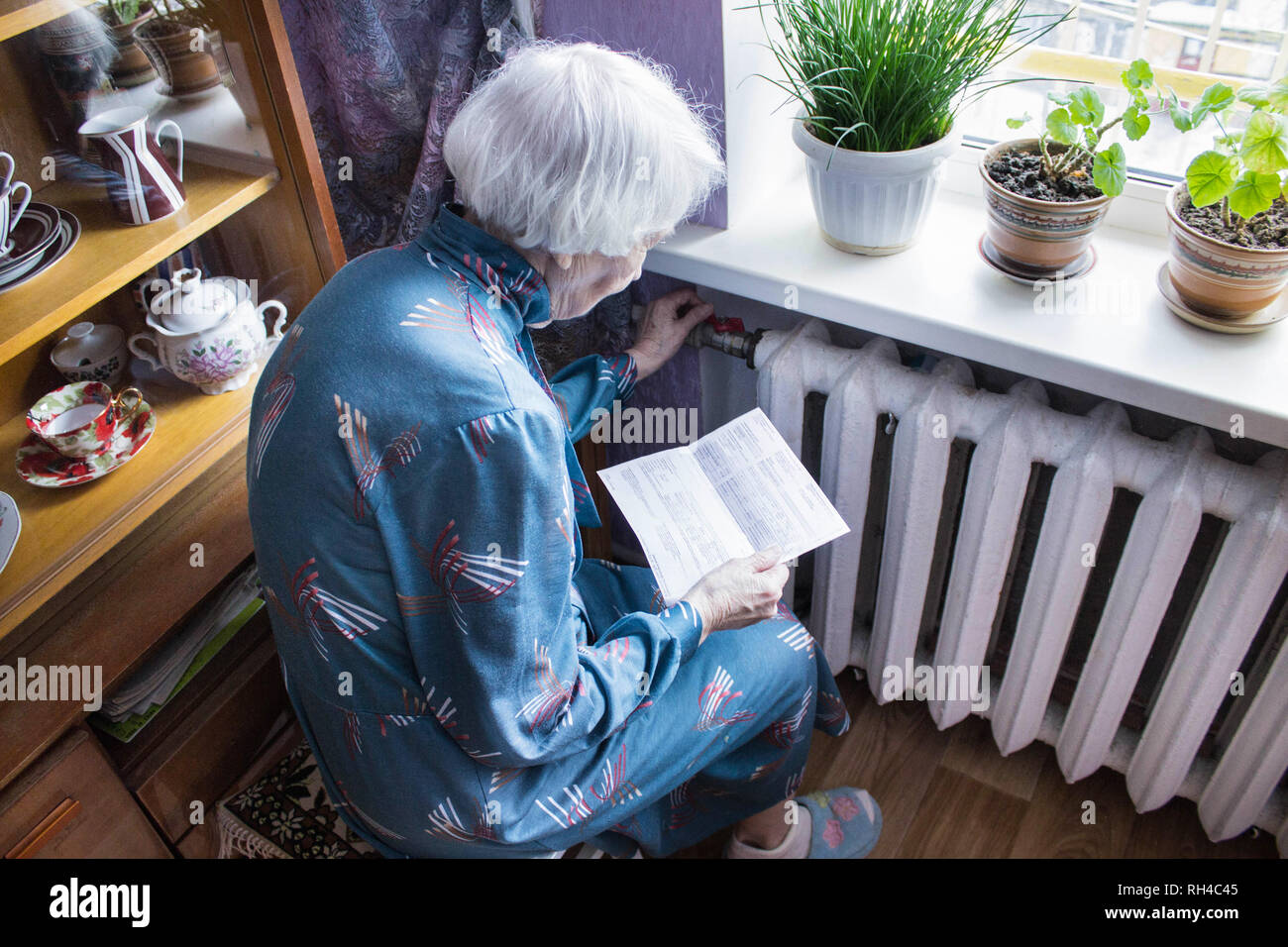 Woman holding cash in front of heating radiator. Payment for heating in winter. Selective focus. - Stock Image