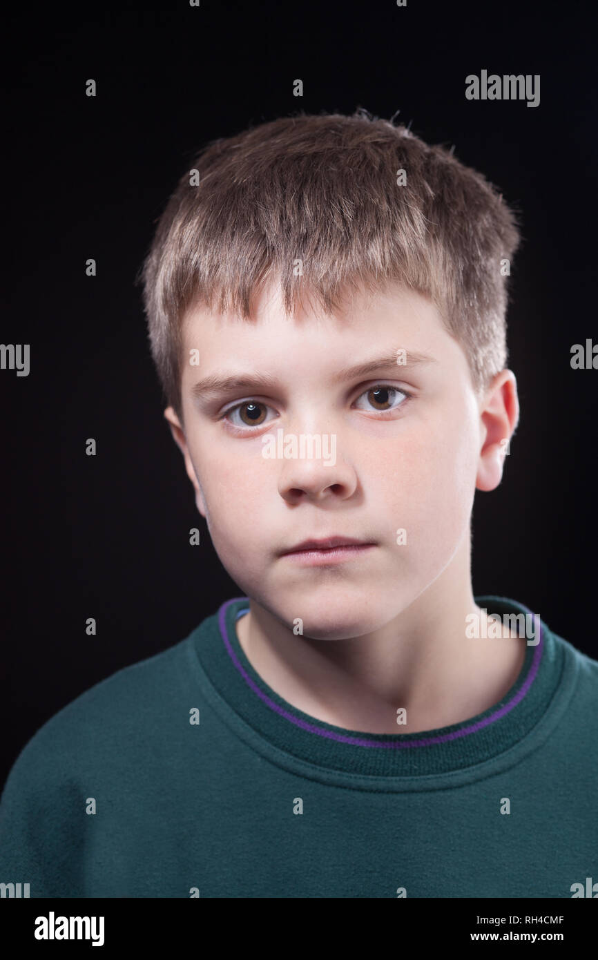 Studio shots of young boy with short brown hair, wearing green jumper - Stock Image
