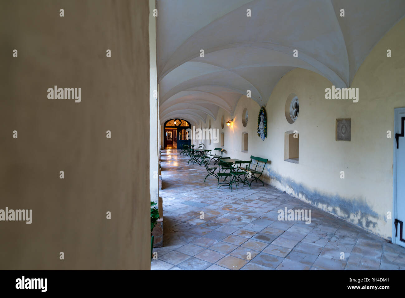 cloister of a convent in bavaria equipped with table and chairs gives a contemplative environment - Stock Image