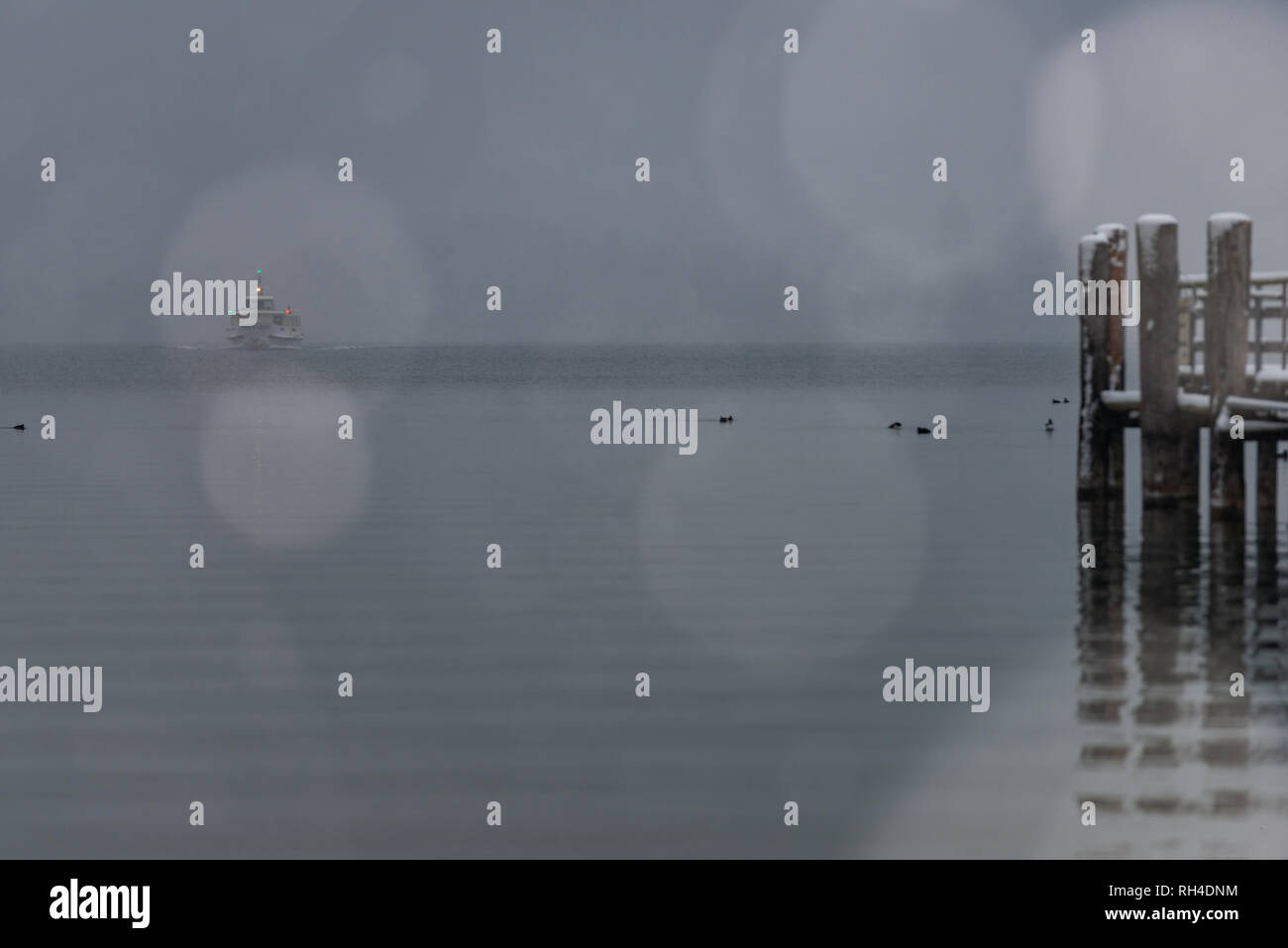 pier on Herrenchiemsee with blowing snow and snowflakes in the foreground - Stock Image