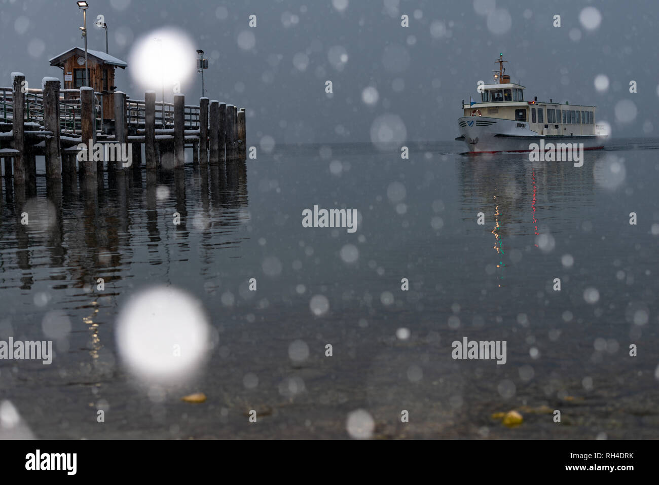 Herrenchiemsee boat in distance with snowflakes in the foreground - Stock Image