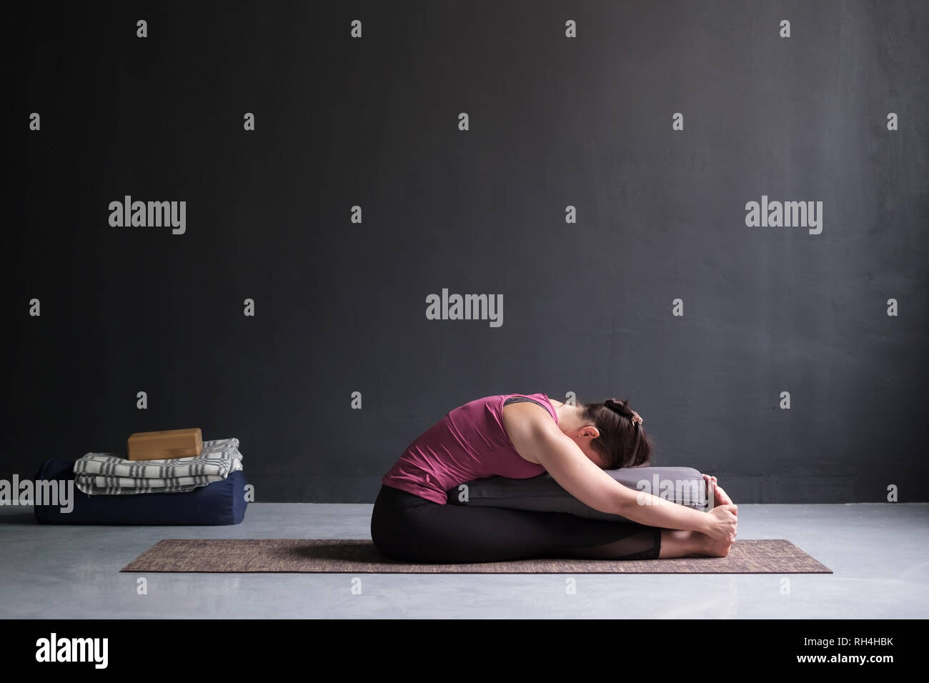 woman practicing yoga, doing Seated forward bend pose, using bolster. - Stock Image