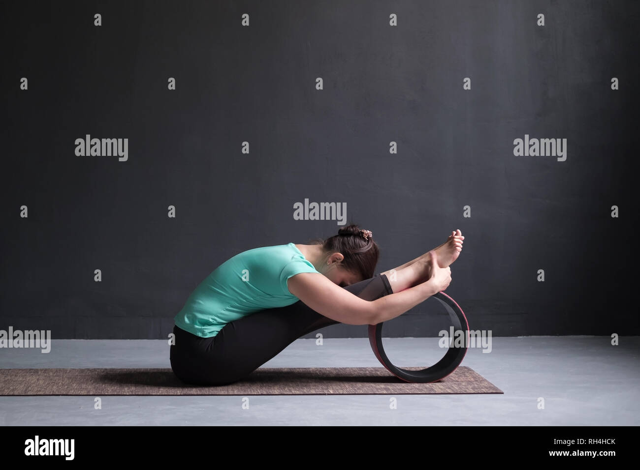 woman practicing yoga, Seated forward bend pose, working out, using wheel - Stock Image