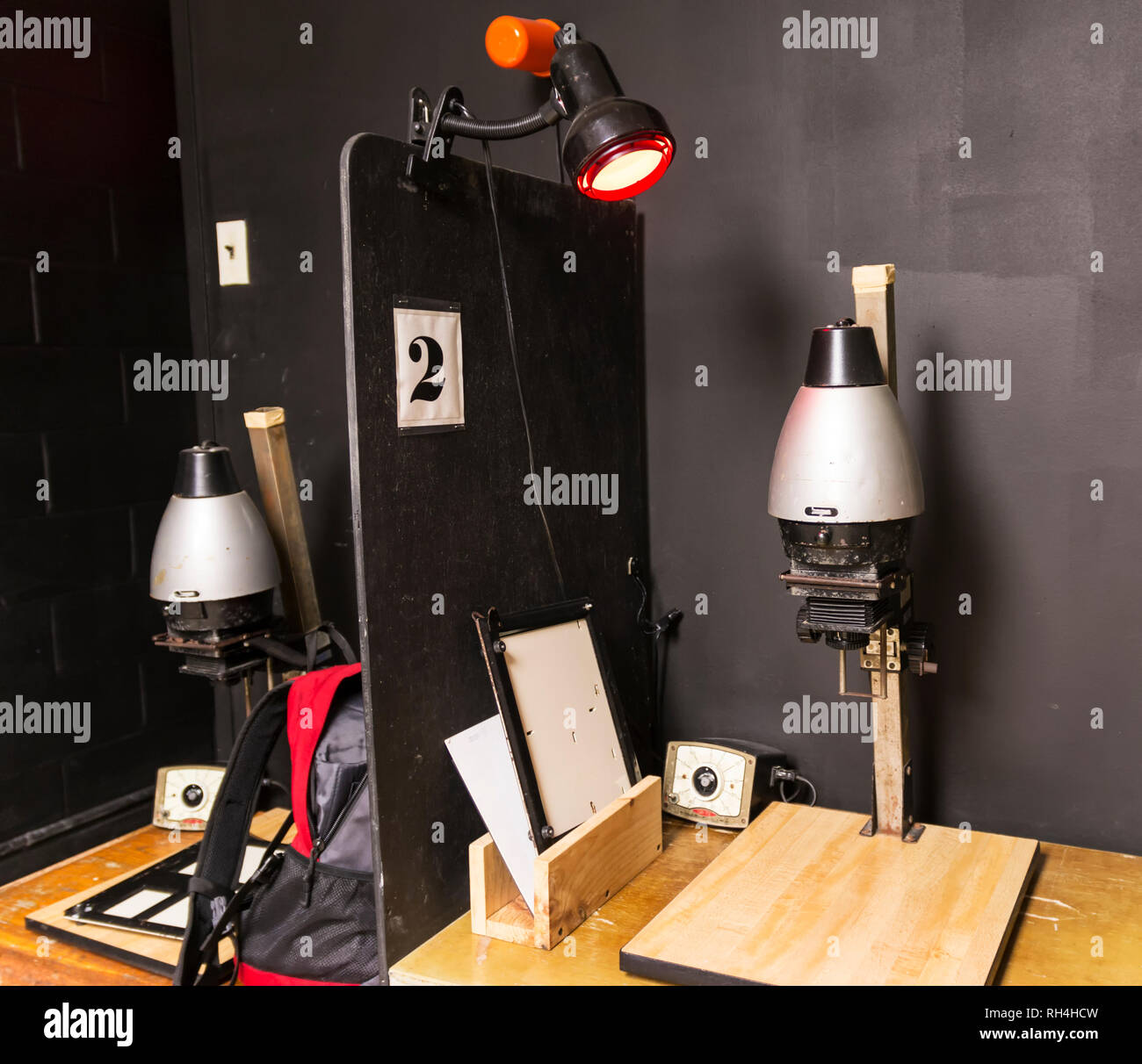 A dark room is set up with old fashion black and white enlargers ready to print pictures. Stock Photo