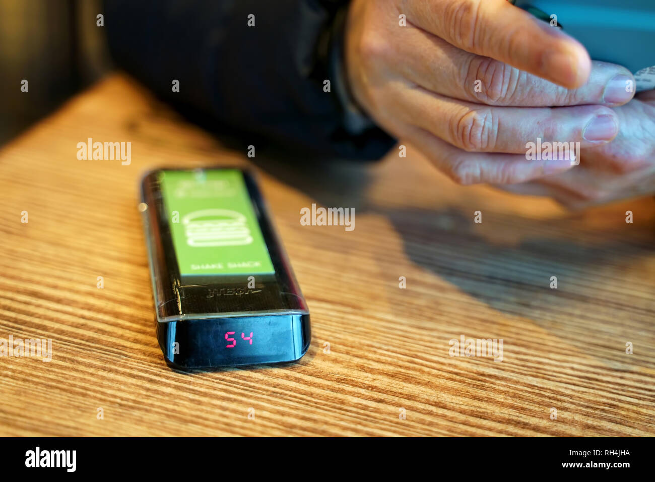 West Hartford, CT USA. Dec 2018. Surfing hands of a restaurant customer waiting for the electronic guest pager to notify of an order status. - Stock Image