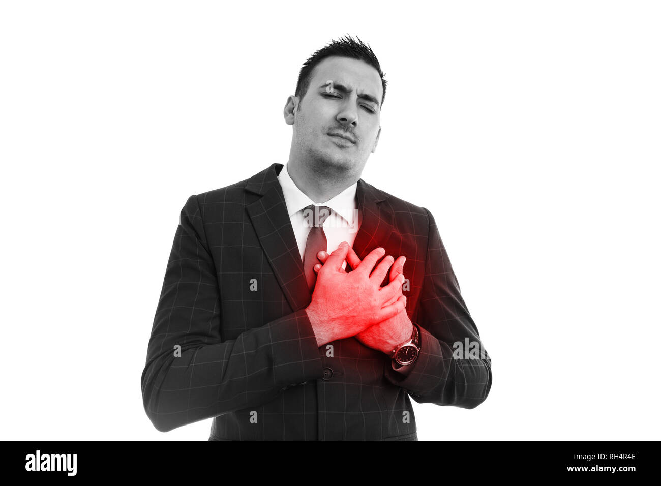 Man wearing suit and tie clutching red heart in black and white image as cardiac health problems concept - Stock Image