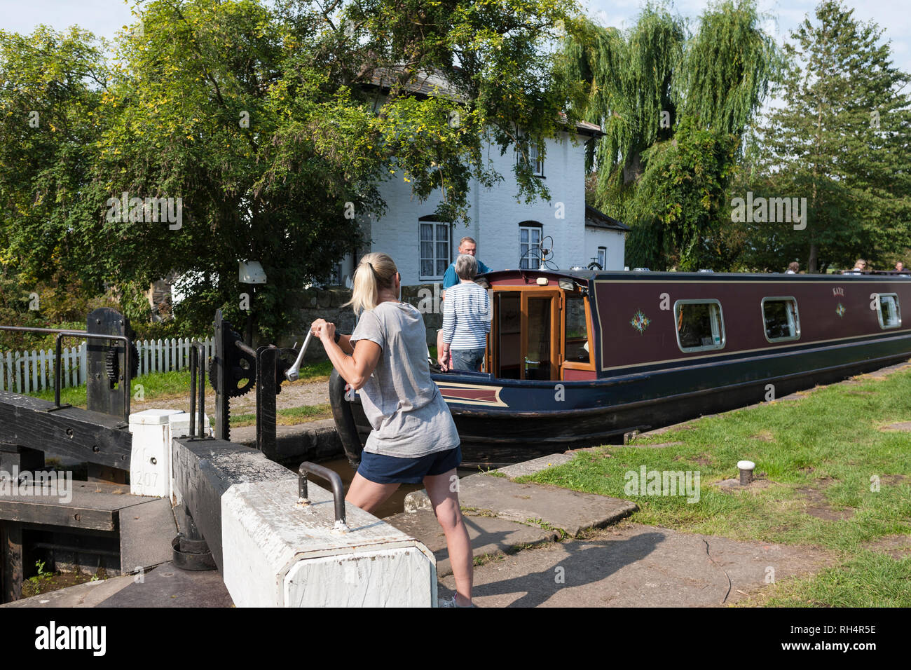 A girl operates the windlass for the ground paddles on New Marton Top Lock No.2, Llangollen Canal, Shropshire, England - Stock Image