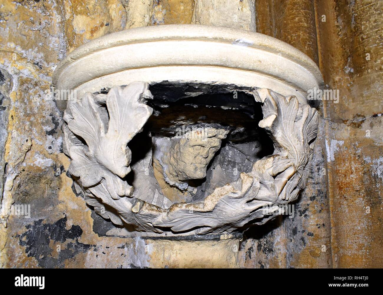 Stone carved face inside a column in Selby Abbey - Stock Image