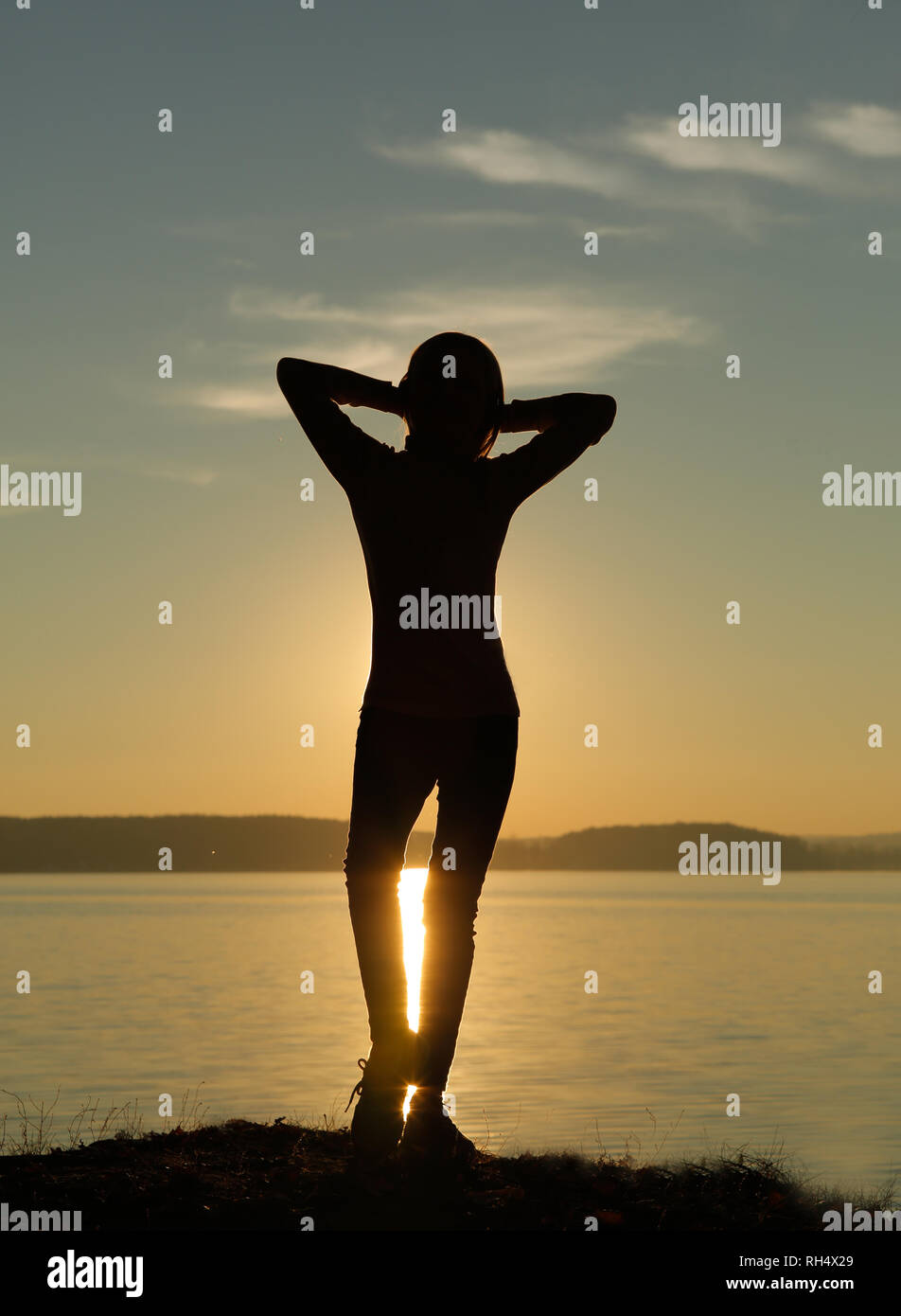 Silhouette of a girl posing in autumn at the sea at sunset - Stock Image