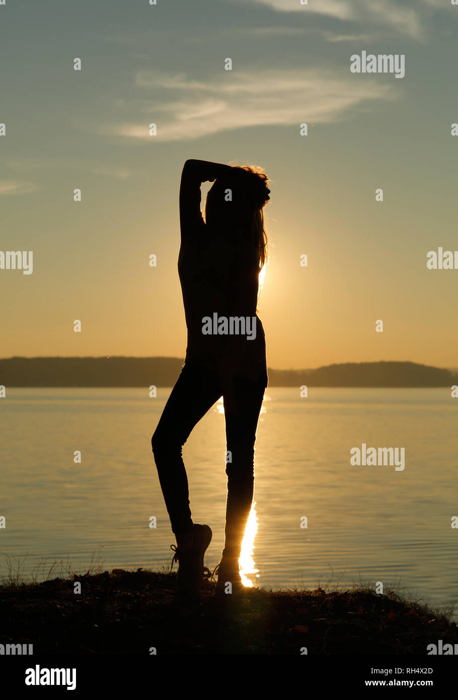 Girl with a beautiful figure at sunset standing posing - Stock Image