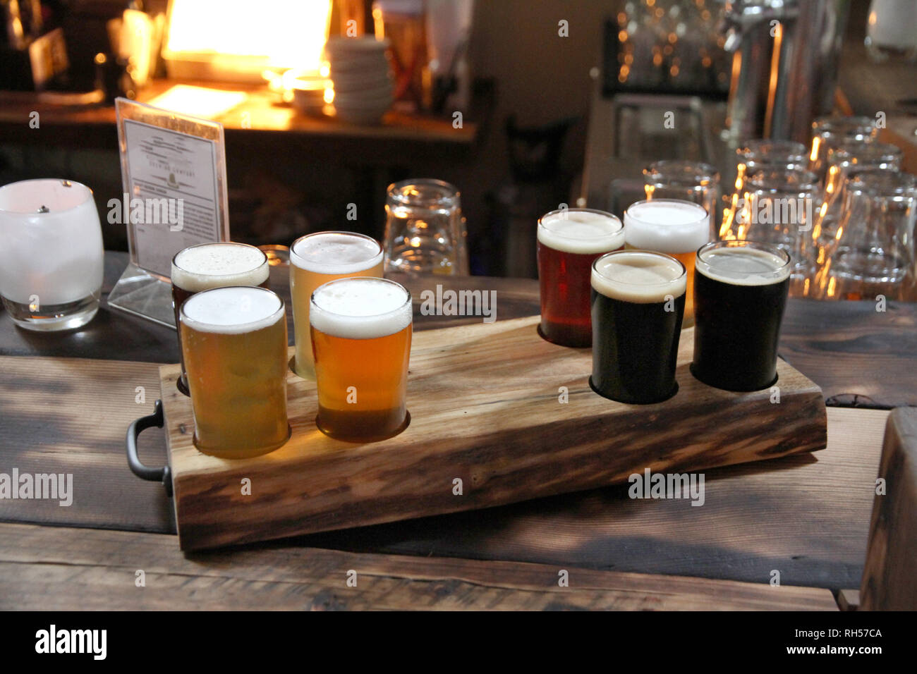 Eight beer samples in a burned wood holder on a burned wood table in a warm room. Stock Photo