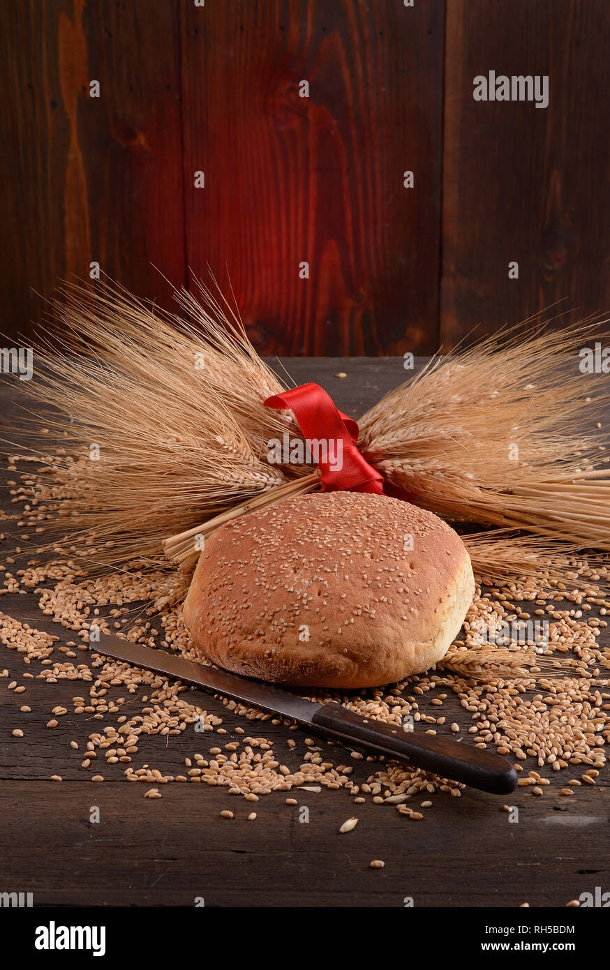 Rustic home-made bread with ears of corn on wooden table - Stock Image