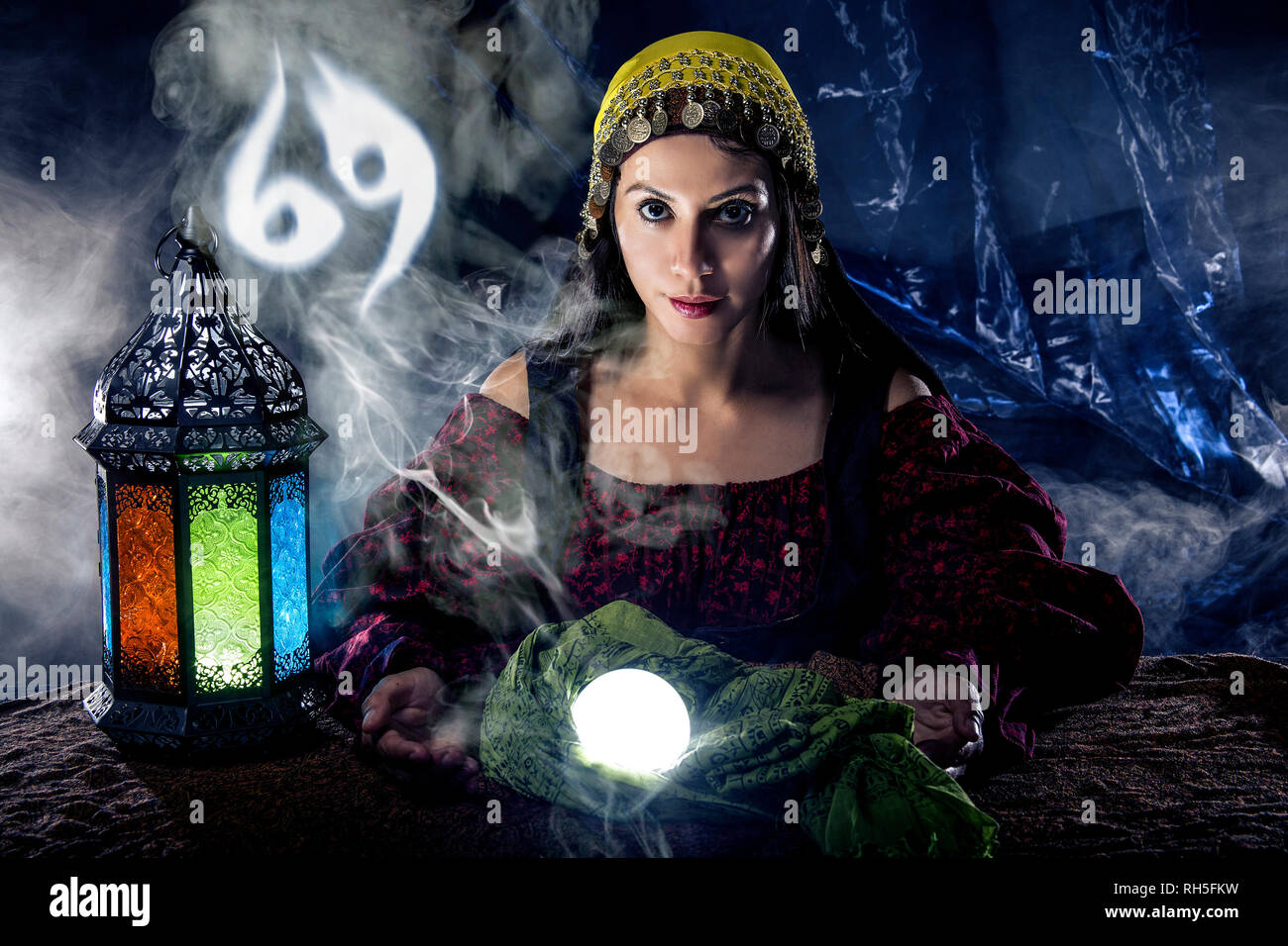 Psychic or fortune teller with crystal ball and horoscope zodiac sign of cancer - Stock Image