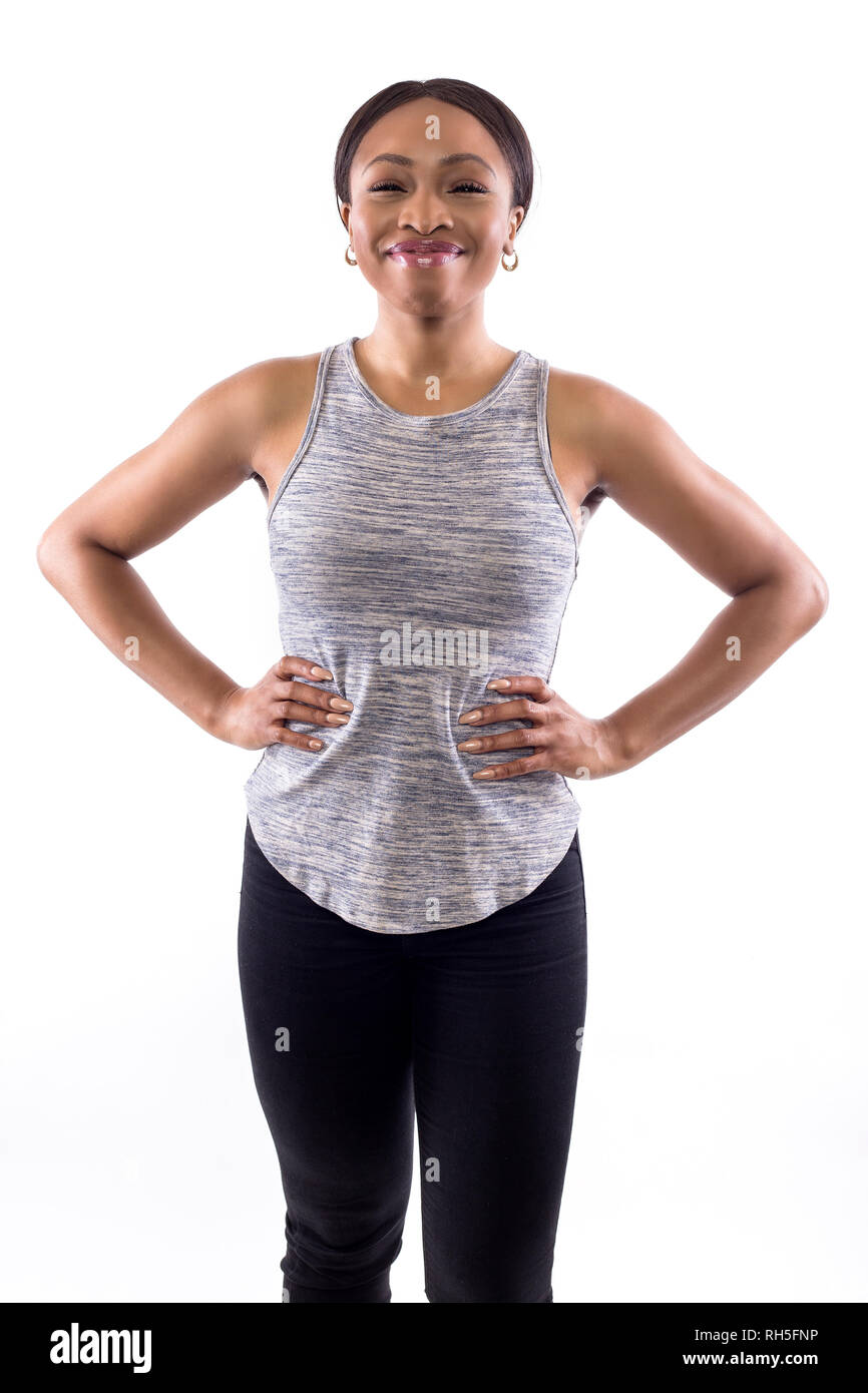 Confident black female wearing athletic outfit on a white background as a fitness trainer - Stock Image