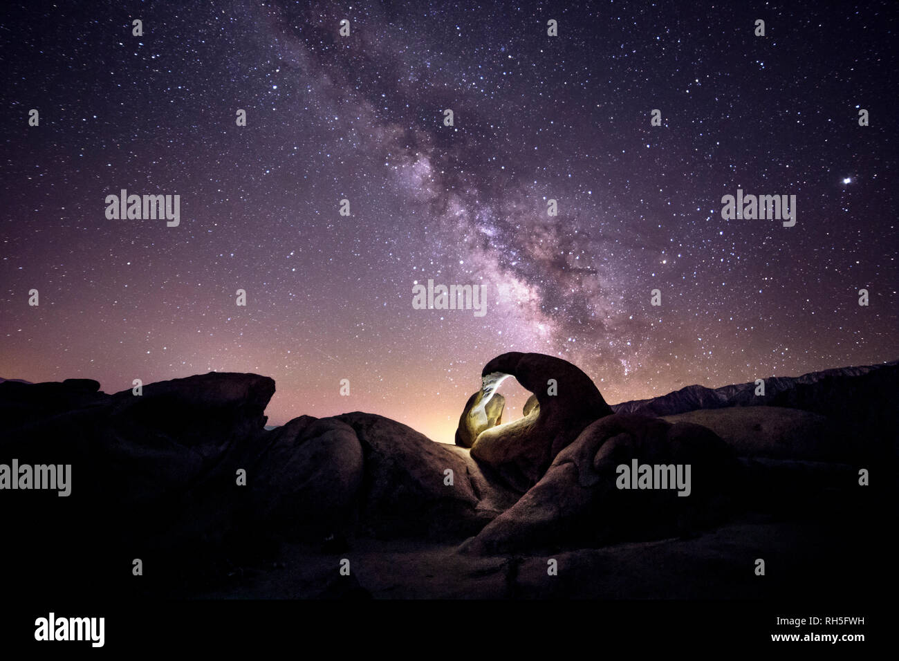 Lanscape view of the desert with stars and milky way galaxy over the night sky.  The image depicts astrophotography and nature.  The universe can be s - Stock Image