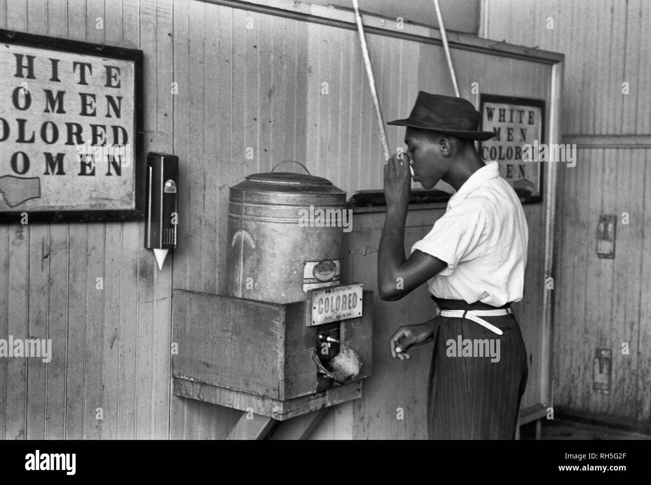 'Colored' drinking fountain from mid-20th century with African-American drinking (Original caption: 'Negro drinking at 'Colored' water cooler in streetcar terminal, Oklahoma City, Oklahoma') July 1939 - Stock Image