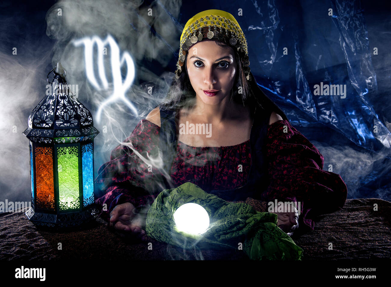 Psychic or fortune teller with crystal ball and horoscope zodiac sign of Virgo - Stock Image