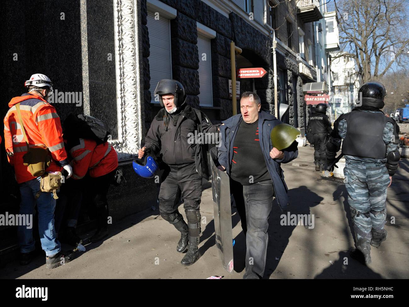 Policeman (Berkut unit) leading protester arrested. Street clashes on Institutskaya street. Revolution of Dignity. February 18, 2014. Kiev, Ukraine - Stock Image