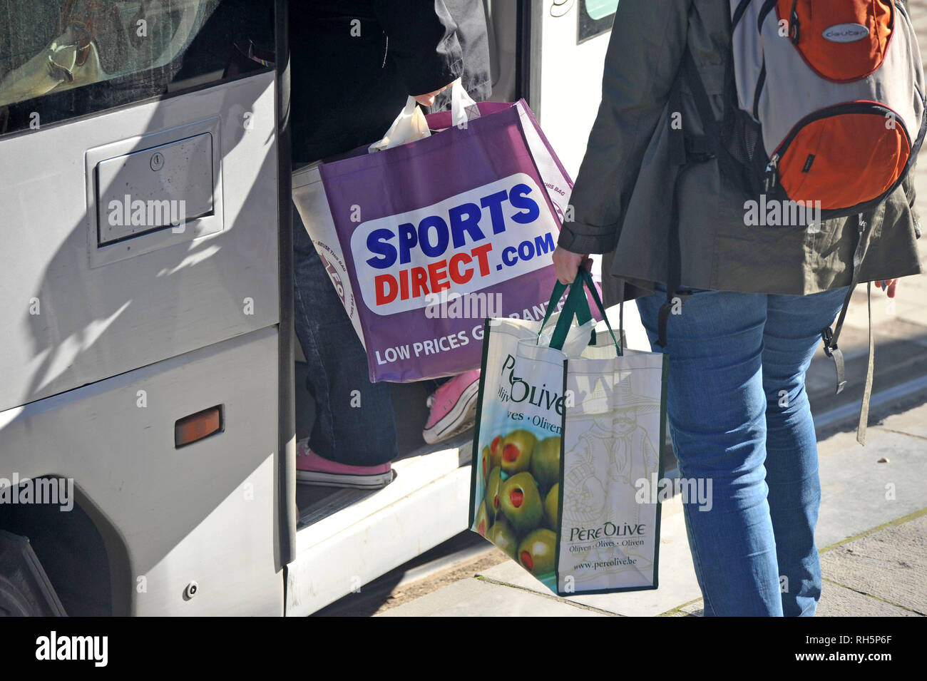 a89522ca1224 Sports Direct shopping bag being carried onto a bus. - Stock Image