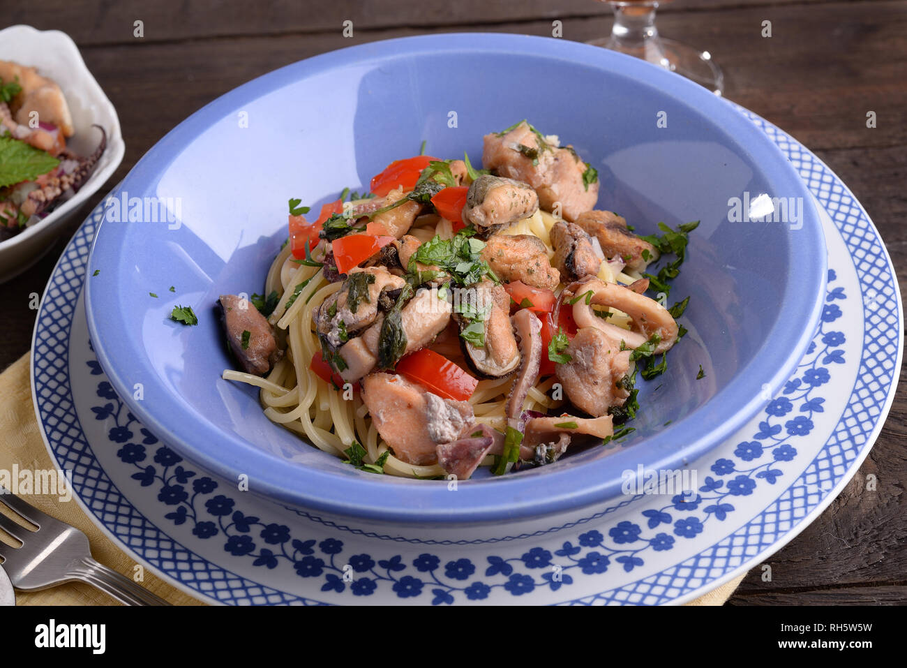 Plate of spaghetti with clams fish and shellfish on wooden table Stock Photo
