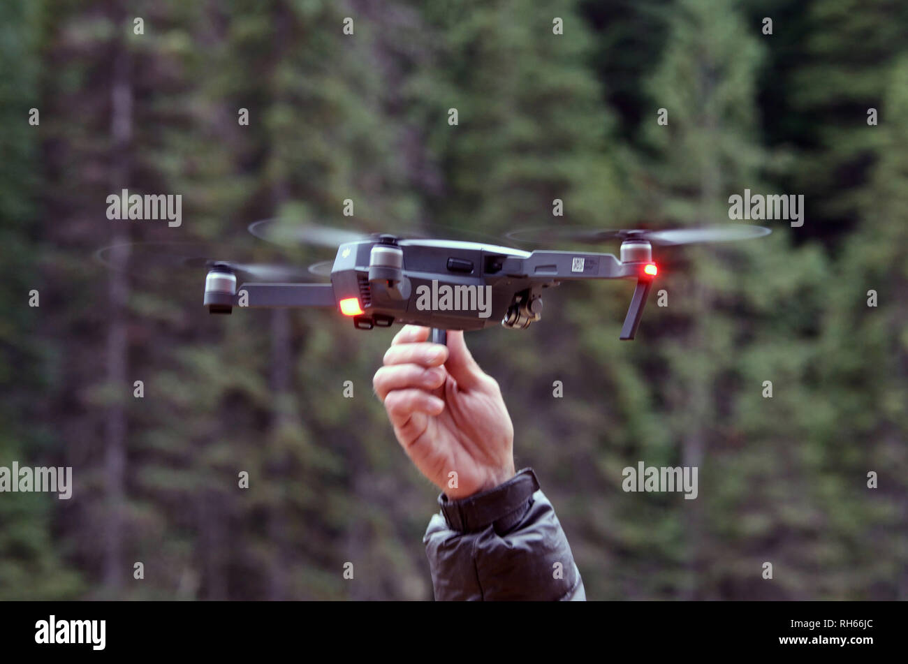 Filmmaker Scott Rulander retrieves a DJI Mavic Pro drone after a videography session in the Purcell Mountains of northwest Montana. - Stock Image