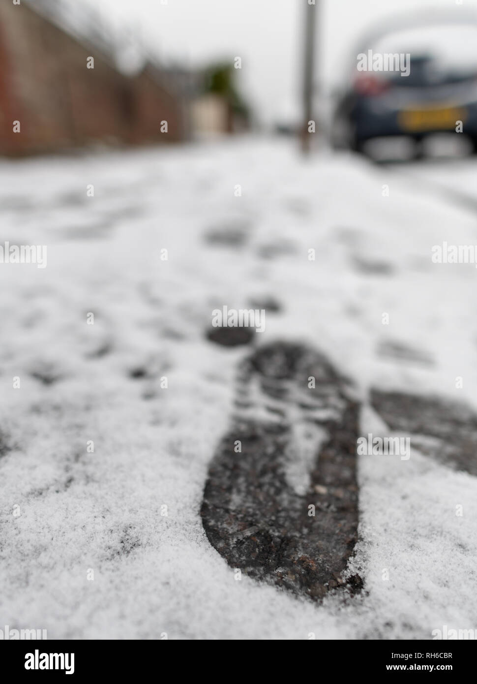 Poole, UK. 1st February 2019. There's snow even in Poole in Dorset, on the south coast of England. Snow in suburbia and footprints on the pavement. Credit: Thomas Faull/Alamy Live News Stock Photo