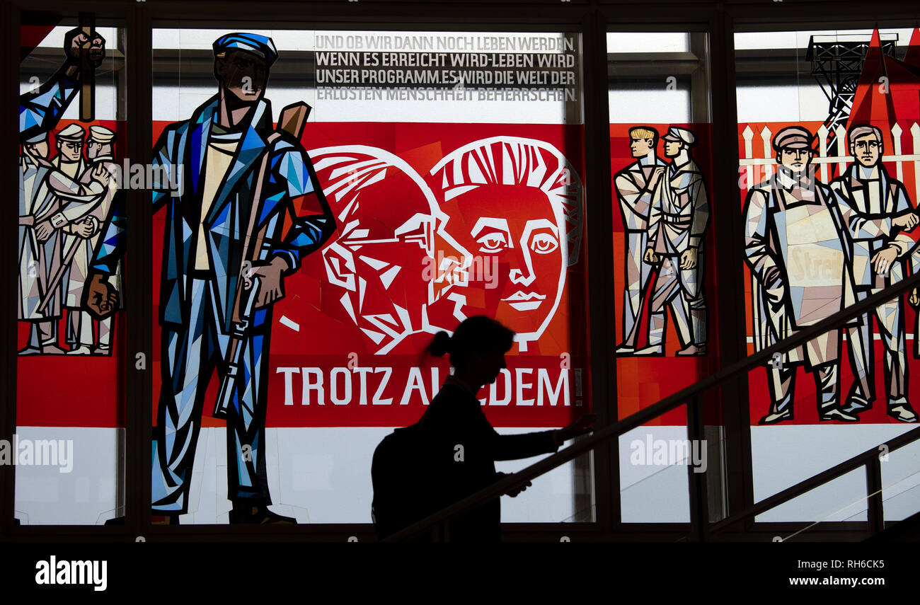 Berlin, Germany. 31st Jan, 2019. A woman walks past socialist art in the atrium of today's European School of Management and Technology in Berlin. The former State Council building of the GDR was built between 1962 and 1964 as the official seat of the State Council. Credit: Ralf Hirschberger/dpa/Alamy Live News - Stock Image