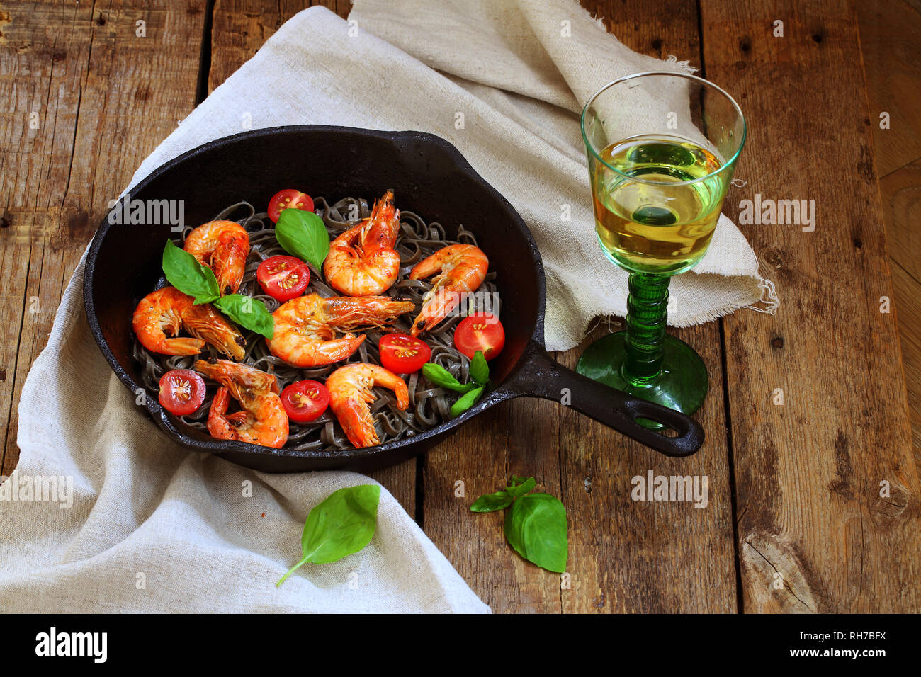 Still life with grilled shrimps and white wine on wooden background Stock Photo