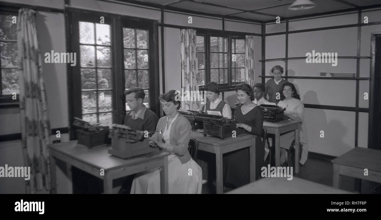 1950s, historical picture of a typing class, showing male and female students sitting at wooden desks using typewriters, England, UK.  From the intoduction in the 1870s of commerical typewriters for office use, the typing machine became an indepensable tool for all writing and correspondence other than personal letters and remained so until being superceded by the personal computer and low-cost laser and injet printer technologies. - Stock Image