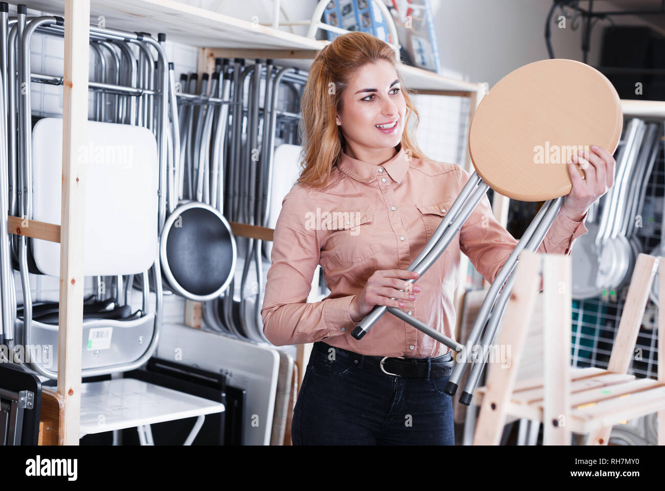 Young happy woman choosing comfortable backless stool in home furnishings store - Stock Image