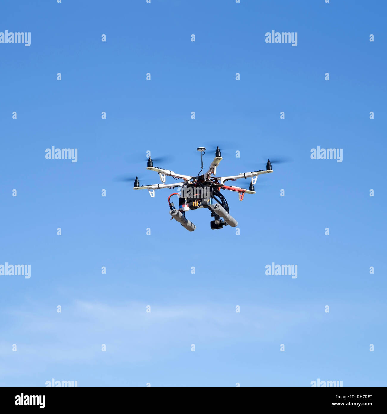 Octacopter drone flying over blue sky - Stock Image