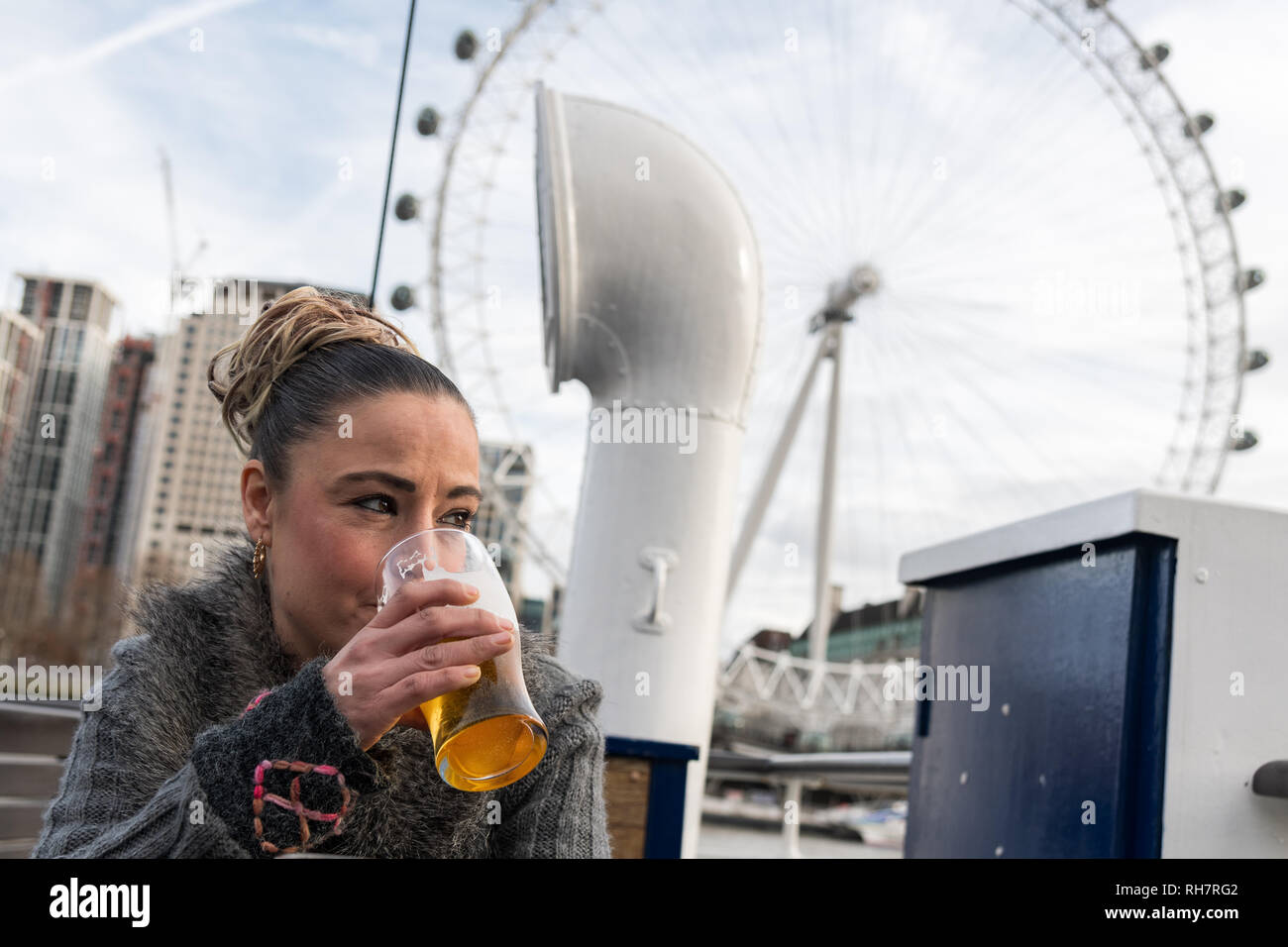 Woman drinking a pint of lager outside the London Eye Attraction - Stock Image