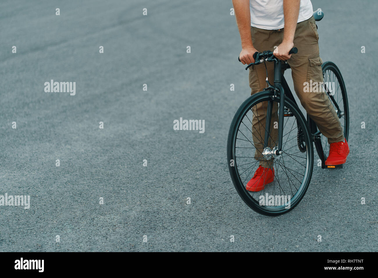 Closeup of casual man legs riding classic bike on city gray road wearing red sneakers and comfy pants. Copy space - Stock Image